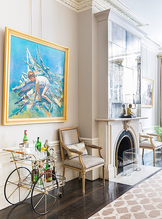 "Antiques and heirlooms—including art gifted ""from my parents and grandparents, which is always special to be able to pass down,"" says Nina—complement the marble fireplace, which is original to the house. The chairs are antique, and the 1940s bar cart sees regular use during predinner drinks."