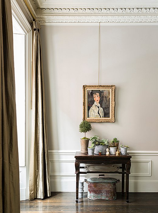 "In the living room, a romantic portrait by Nina's mother hangs above an Indonesian altar table that Nina made into a perfect plant stand: ""I find corners of rooms need a little life, so it's best to keep plants there."""