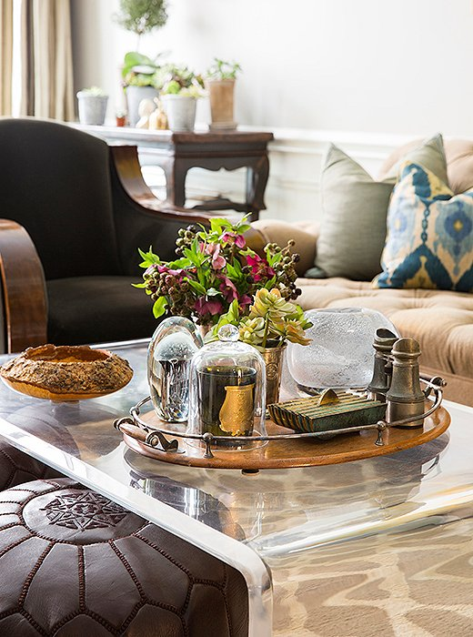 "A sturdy Plexicraft waterfall coffee table is topped with favorite objects, from a Cire Trudon candle (""My favorite scent is Pondichery. It reminds me of an Indian spice market"") to sculptural glass vases."