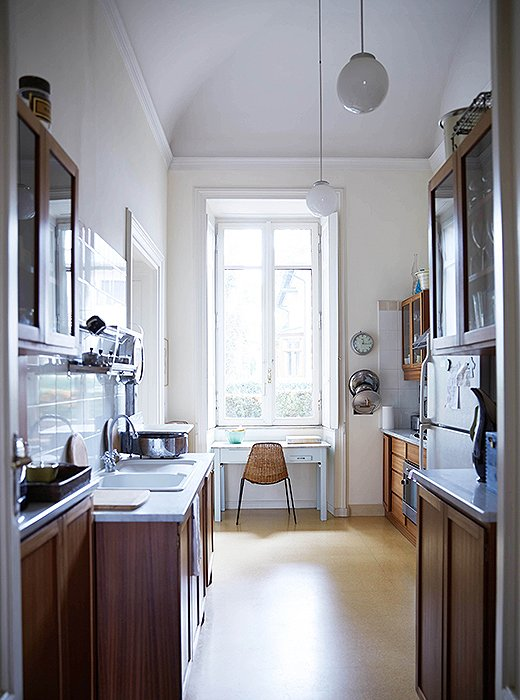 Even in the narrow kitchen, the apartment feels villalike with its soaring arches and long windows.