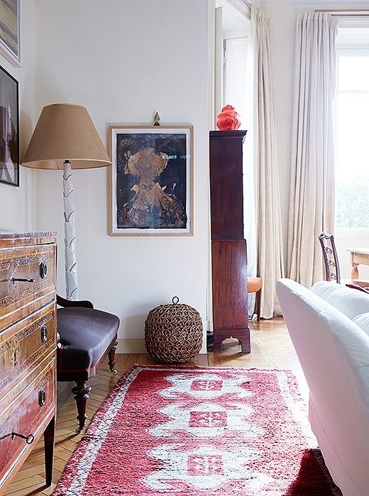 The red in this Turkish rug works with the red on the sofa—as well as the hot red of the ceramic piece atop the highboy.