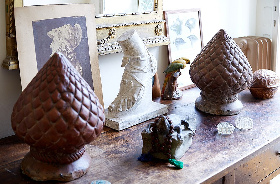 By the hallway to the garden, Peter arranged a tableful of objects—a French plaster cast of the foot of the Apollo Belvedere, Neapolitan pinecones made of terracotta, and a papier-mâché alligator wearing an emerald necklace.