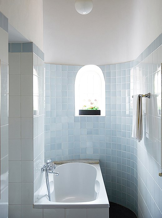 "Of this bathroom's rounded shape—which gives it a chapellike atmosphere—Peter says, ""This space was originally a servant's staircase. Now when you're lying in the bath, you can see the round opening up top."""