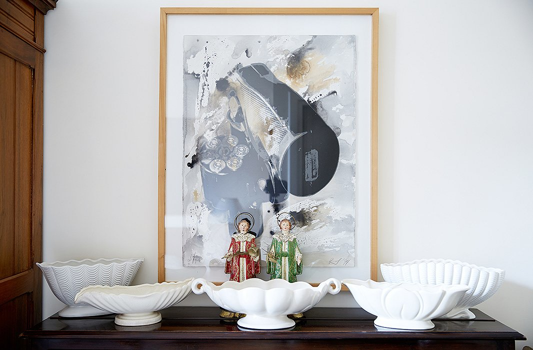 A 1990s lithograph by American artist Robert Longo leans behind another assemblage of white vessels.