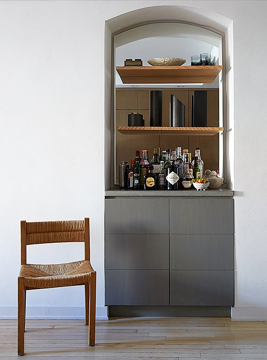 Samuel transformed a bookshelf into an alluring smoky-gray bar by gutting the space and installing a mirror with cove lighting underneath. The lower section is a hideaway spot for television equipment.