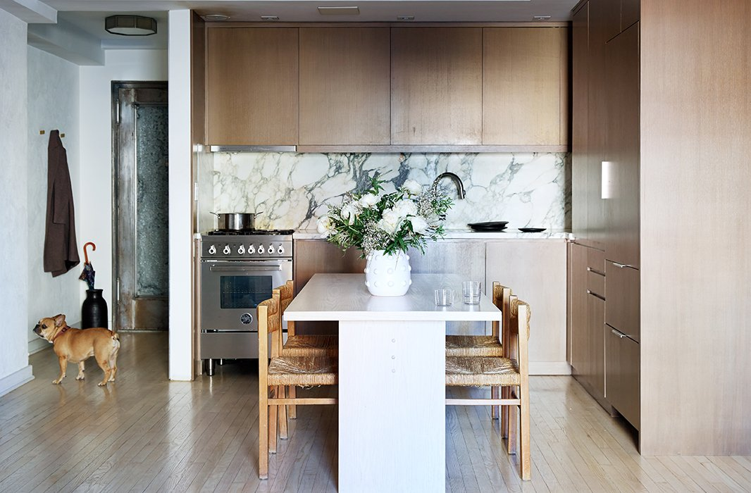 The Italian-marble kitchen backsplash, with its blown-up patterns, sets the gray palette of the apartment. Samuel cooks every day (unlike most New Yorkers), and when entertaining a crowd, he pulls the vintage dining chairs over to the sofa to seat 10 for dinner.