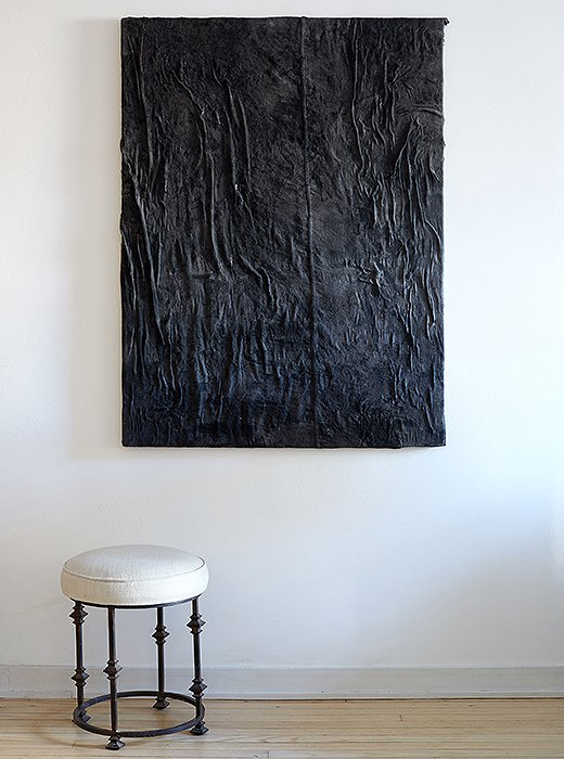 An ultratextured painting by Alex Fideli hangs above a stool of Samuel's design. Even the backdrop brings dimensionality and rough-and-tumble texture: The floors were bleached and pickled to reflect more light, and the walls were plastered to be a little rough.