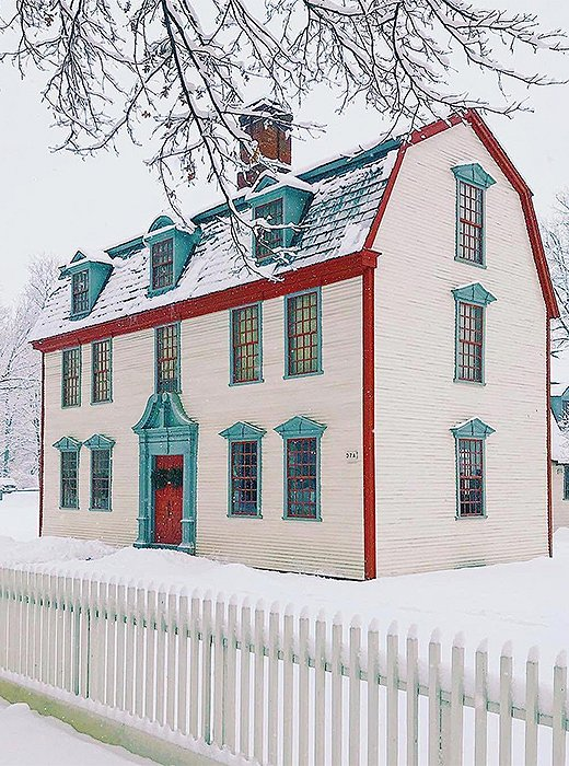 A mansard roof trimmed in red and dusted with snow. Photo by @howieguja.