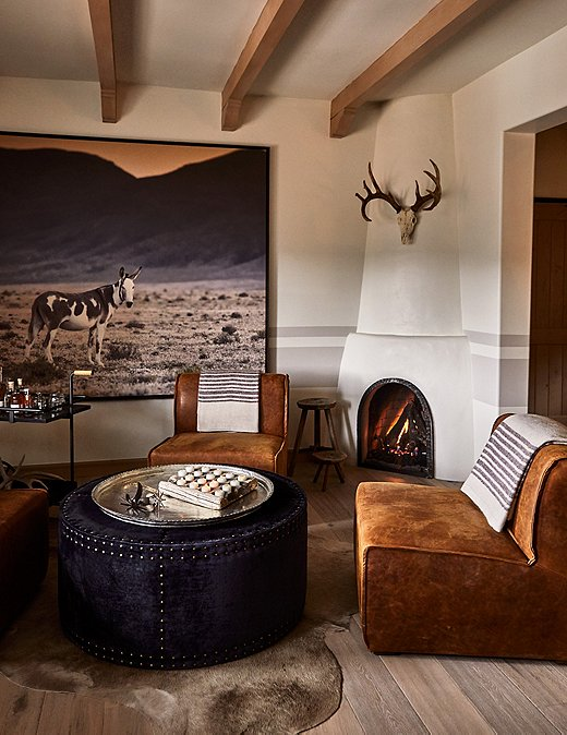Each room features specific nods to the history of Bishop Lodge. In this guest room, leather chairs and hide rugs add depth, with oversize photography creating a focal point.