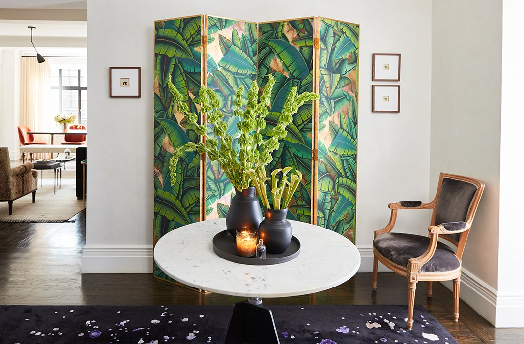 In Bennett Leifer's foyer, Venetian plaster walls amplify the natural light from neighboring rooms. A palm-leaf print de Gournay screen and a rug by Edward Fields, custom-made for Bennett's room at the 2015 Kips Bay Showhouse, create an intriguing interplay of color and pattern.
