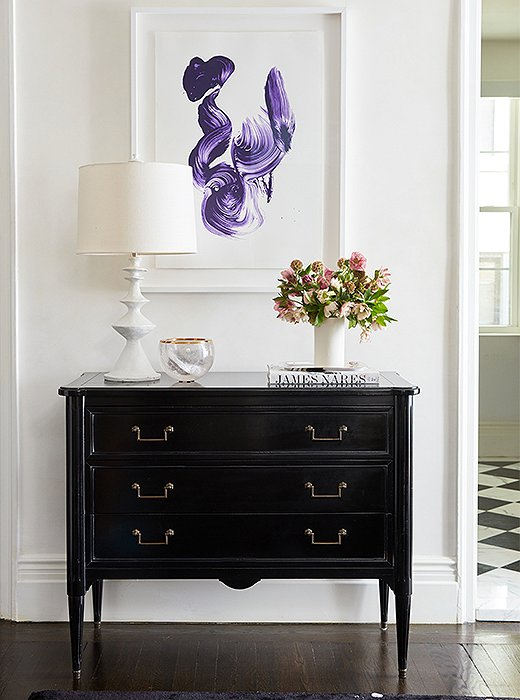 Elsewhere in the entryway stands a black chest topped with a plaster lamp and a rock-crystal bowl. Above, a contemporary stroke of purple by artist James Naras hangs in conversation with the splatter-print area rug below.