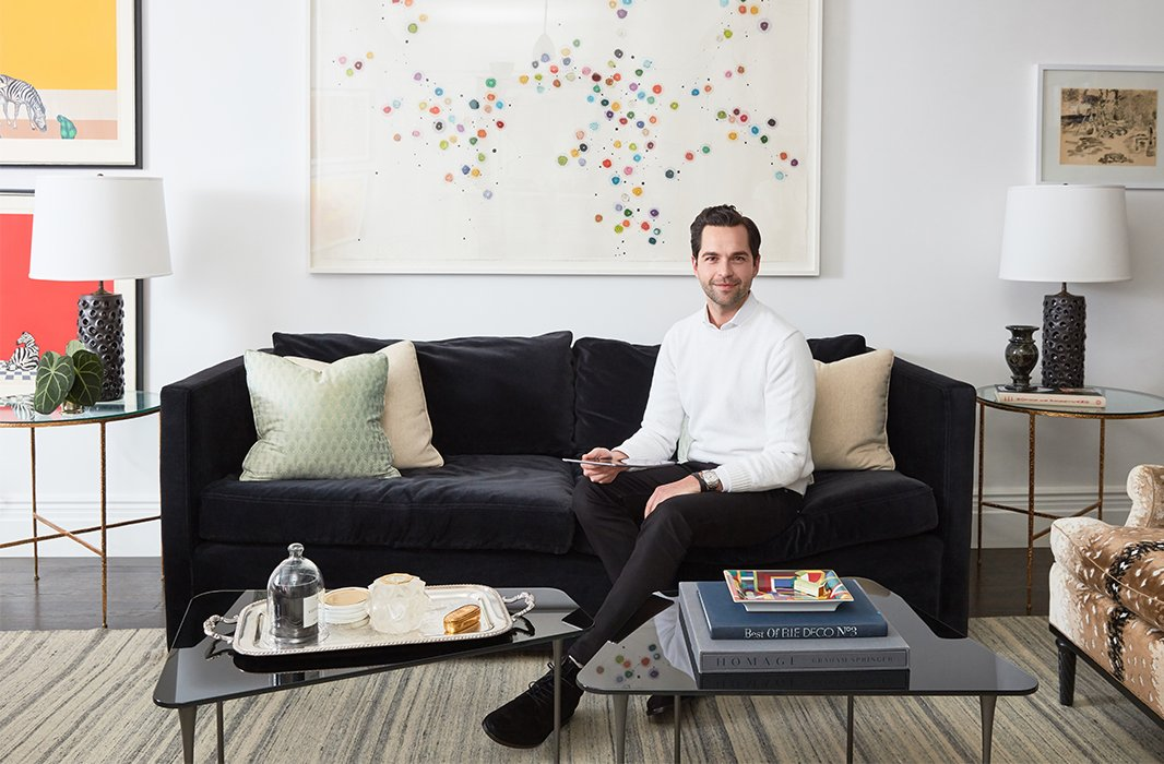 Designer Bennett Leifer in his apartment's living room, where a pair of cocktail tables and a velvet sofa create a cozy conversation area. The large-scale artwork is a painting by Minjung Kim titled Predestination. The English silver tray adds a note of traditional polish.