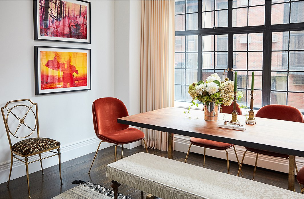 A Marc Bankowsky bench sits on one side of the live-edge dining table, providing ample seating while keeping sight lines open. Contemporary chairs in a rich orange velvet pick up on the warmer tones of the adjacent photographs—and, paired with an ornate brass side chair and classic candlesticks, make for a stylish mix of old meets new.