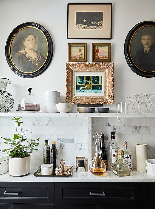 A medley of vintage artworks lends spirit to the black-and-white kitchen. The slim marble countertop and shelf house a tightly curated collection of barware, kitchen accessories, and serving pieces.