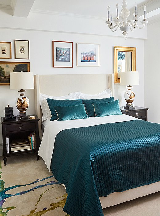 In the master bedroom, the custom carpet's turquoise streak matches the hue of the bed's quilt and pillows. Classical lamps by Parzinger and a milky Murano glass chandelier light the space—a pairing as eclectic as the gallery wall surrounding the upholstered headboard.