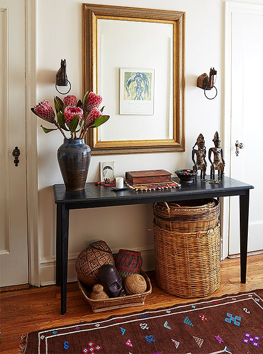 "African sculptures grace the entry's console table, beneath which sit baskets collected from near and far. ""I've always kept my savings for travel,"" Hardison says. ""Travel is important."""