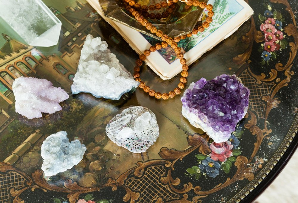 "An antique side table in Shiva's living room is topped with a few of her crystals: amethyst (""for spiritual growth and healing""), smoky quartz (""for grounding and anchoring you to Mother Earth""), and a heart-shape quartz (""for personal growth"")."