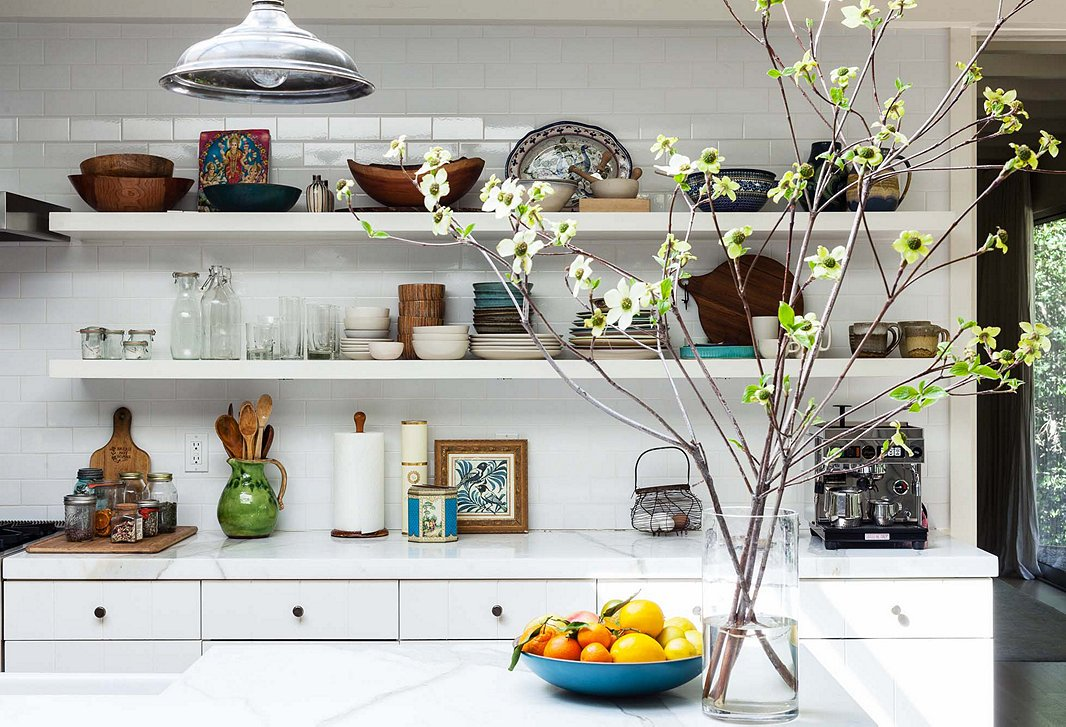 Subtle pops of color, an edited mix of dinnerware, and a spray of fresh tree branches help this kitchen embrace bohemian flair. Photo by Nicole LaMotte.