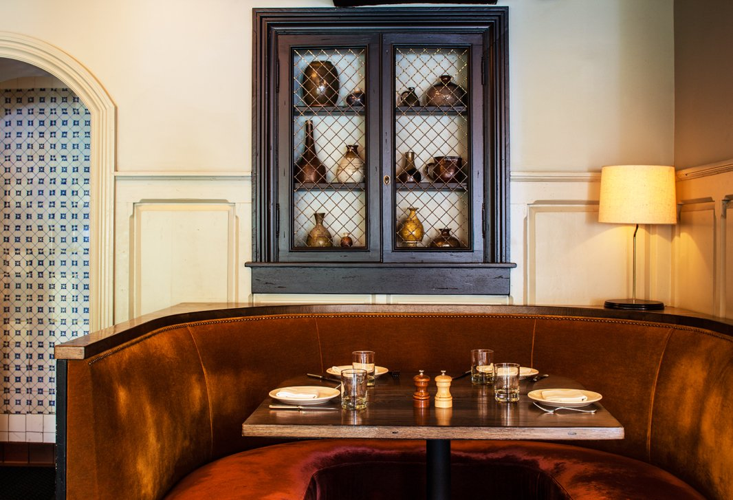 A burnt-orange mohair banquette is a holdover from the previous restaurant. Behind it, a wine cabinet houses pottery Claire scored online.