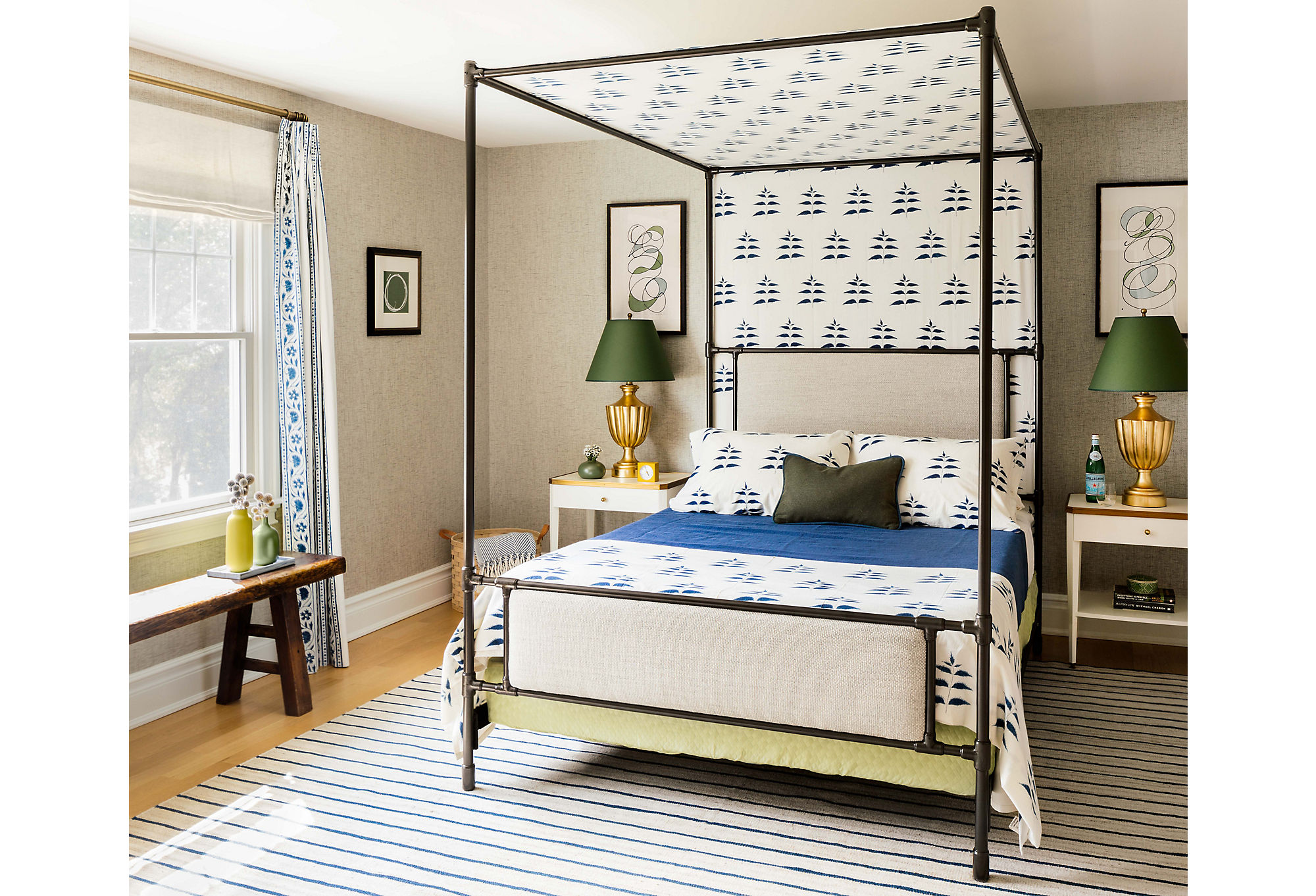 Pattern takes center stage in the guest room. The bed is draped in fabric from Les Indiennes. Gold table lamps add a pop of metallic brilliance.