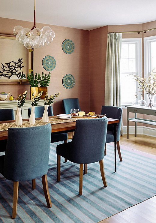 """""""I wanted to find a color that could hold its own,"""" says Chauncey of her choice to go pink in the dining room. The grass-cloth wallpaper adds color with subtle elegance. The decorative bowls serveas wall art loaded with texture."""