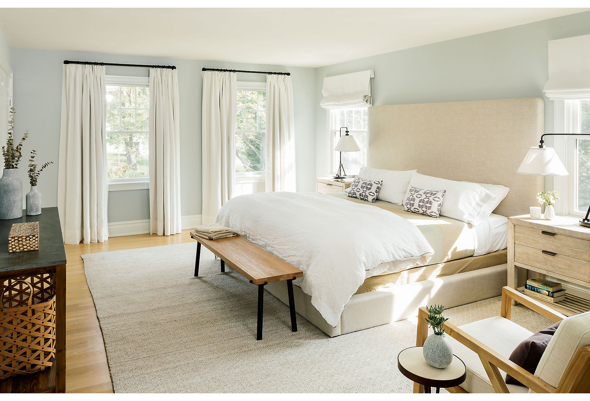 The couple gravitated to more-industrial elements, so Chauncey set about softening that look in the master bedroom with simple white drapes and a muted palette. The room is painted in Horizon from Benjamin Moore. Table lamps from Ralph Lauren Home serve as bedside lighting.