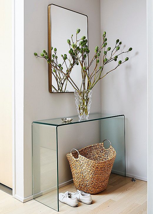 OurSomerset Wall Mirrorsits over aglass waterfall console table in the entry. A woven basket and greenery add natural warmth.