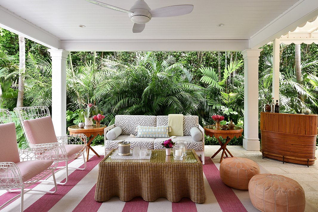 """""""This area is an extension of their home; they really live out there,"""" says Caroline of the home's loggia. With performance fabric and outdoor-approved furnishings, Caroline was able to create a colorful escape. The outdoor spaces came to life with the help of landscape architect Fernando Wong. """"He really took this house and made it so charming,"""" says Caroline."""