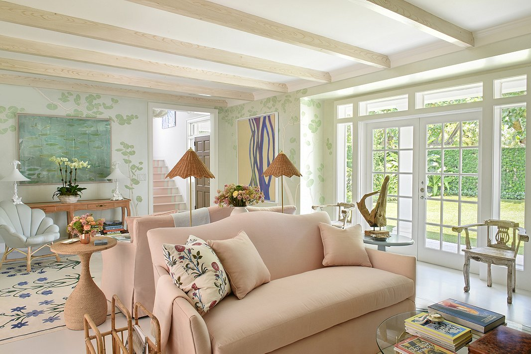"""The mural on the living room walls was inspired by the family's beach club. """"We ran with it and made it her own,"""" says Caroline. She placed two blush sofas back-to-back to maximize the room's long layout. Textures come alive in this space, with Caroline mixing jute with rattan with driftwood. (Find the rope-covered side table here.) The result is a room that feels classically coastal without being too beachy."""