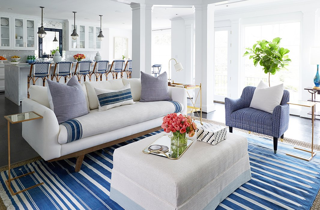 "The custom-sized throw, wrapped around both sides of the seat cushion, protects the couch with a ""washable barrier,"" as Cassie puts it, for any spills. The cushions add more layers of washable fabric and ramp up the easy, colorful style."