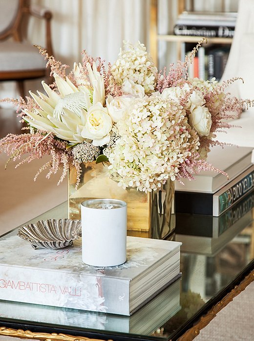 Metallics consistently run through the home's design. Here, a bold geometric vase plays off the stylized leaflike motif along the gilded coffee table.