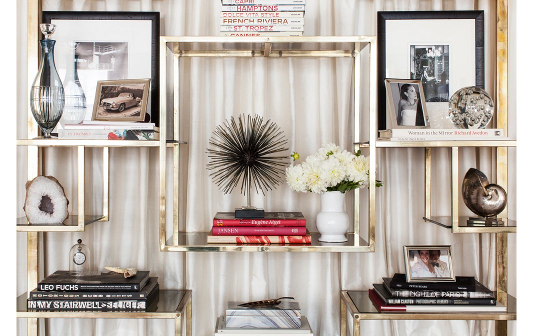 Each shelf is like a lesson on how to make a perfect vignette: Pile books by color, and perch one strong accent atop each stack.