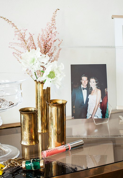 On the entry table, snapshots of the couple and family are mixed among mini brass vases and, of course, handy Chantecaille lip glosses.