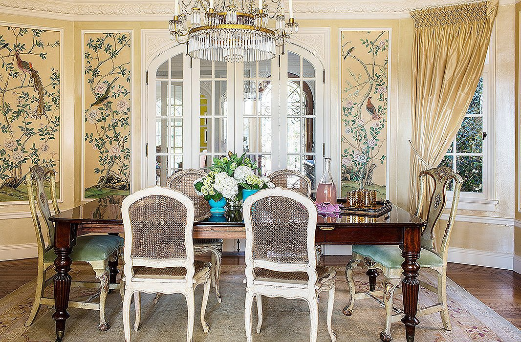 The glossy turquoise flowerpots on the table provide a pop of bright color. Even without them, though, this dining room would be far from monotone, thanks to thefanciful wallpaper panels and the coordinating green velvet upholstery.