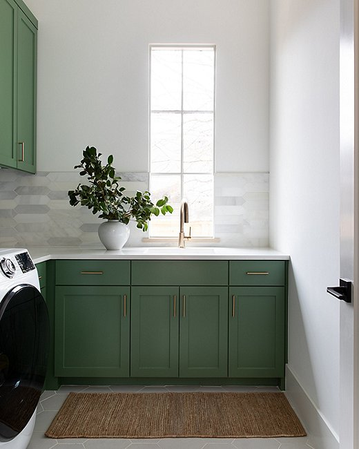 """""""I wanted a fun, cheery pop of color here,"""" says Christina of the laundry room. She painted the cabinetry a classic shade of Calke Green from Farrow & Ball."""