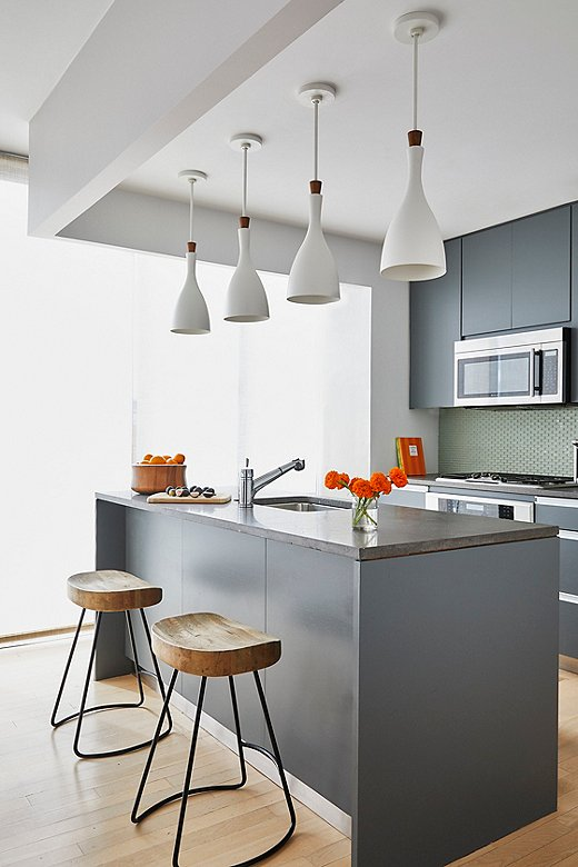 Modern white pendant lightsadd a nice curved shape to the kitchen vignette. Wooden counterstools bring some natural warmth.