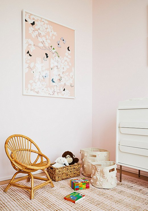 Dawn Wolfe butterfly arttakes center stage in the nursery.Storage baskets from Pehrkeep toys organized without taking too much space, and, because they're canvas, they can easily betuckedaway when not in use.