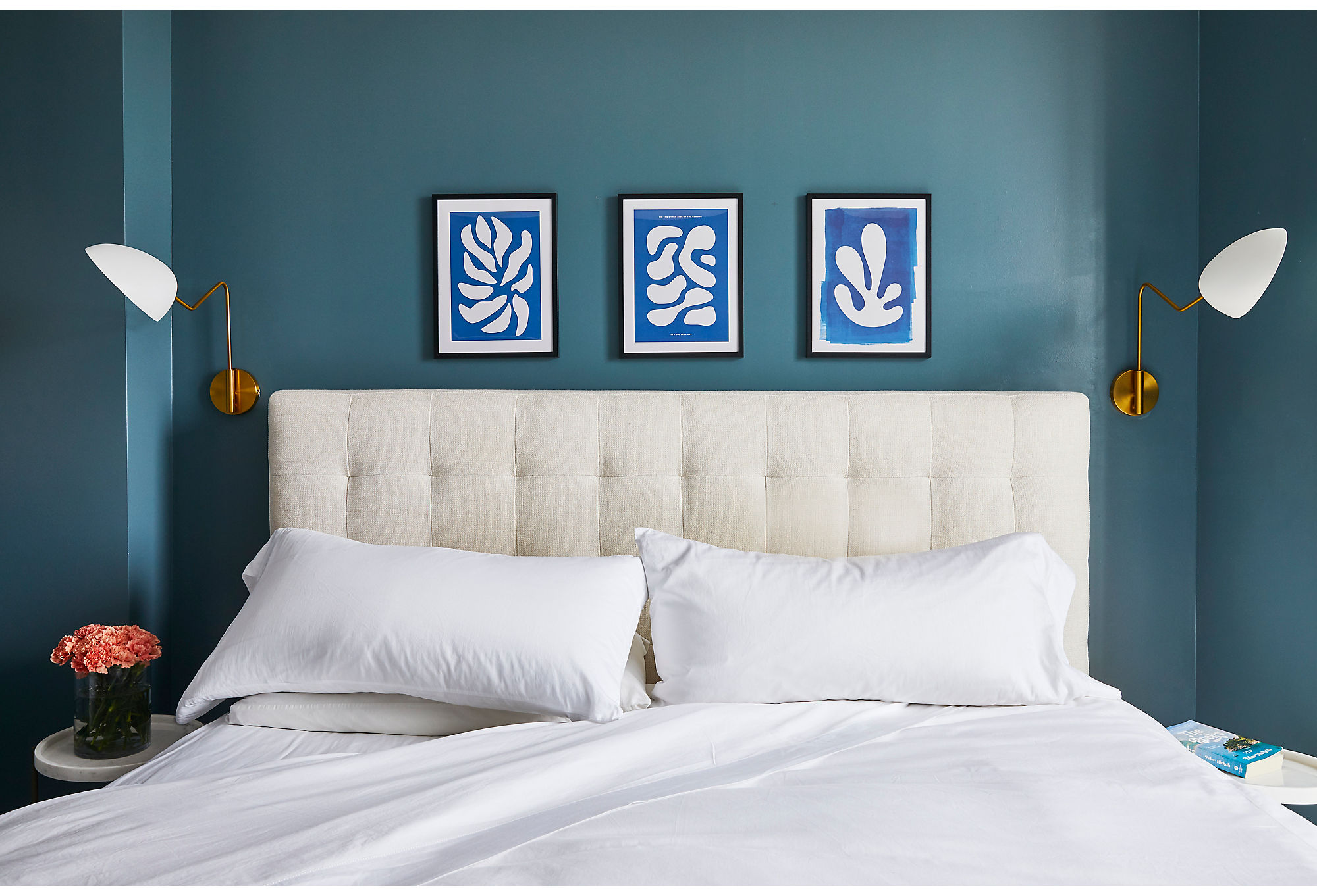 A tufted headboard (see a similarbed here)and crisp white linenscreate a serene place for the couple, who work high-stress jobs, to lay their heads. Streamlined sconces flank the bed, allowing the trio of Matisse prints tobe the star of the show.