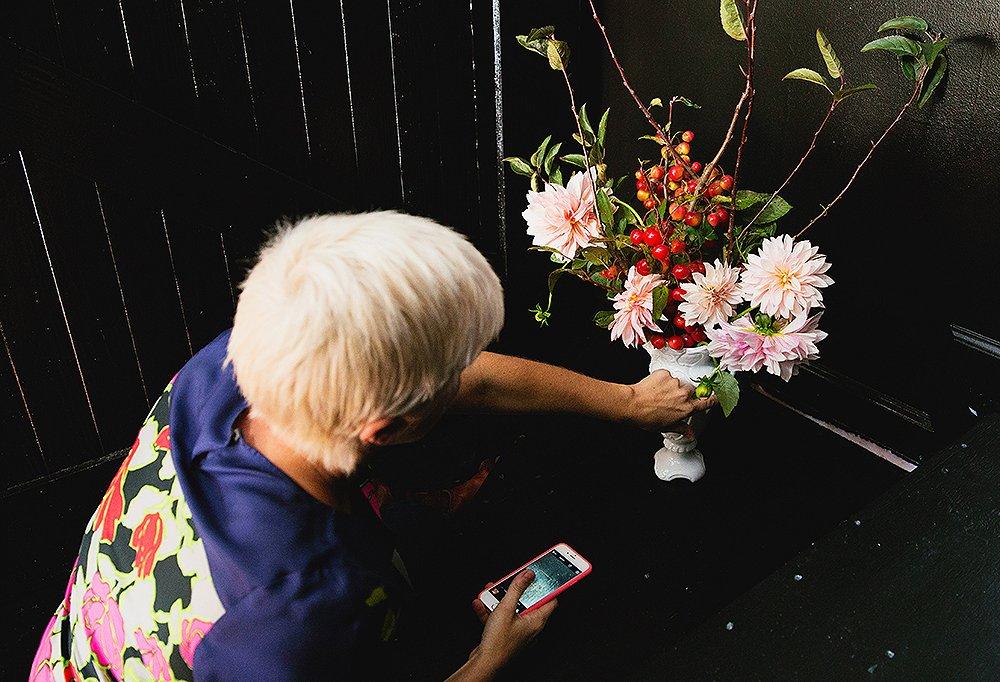 Bailey tests an arrangement against a pitch-black painted backdrop.