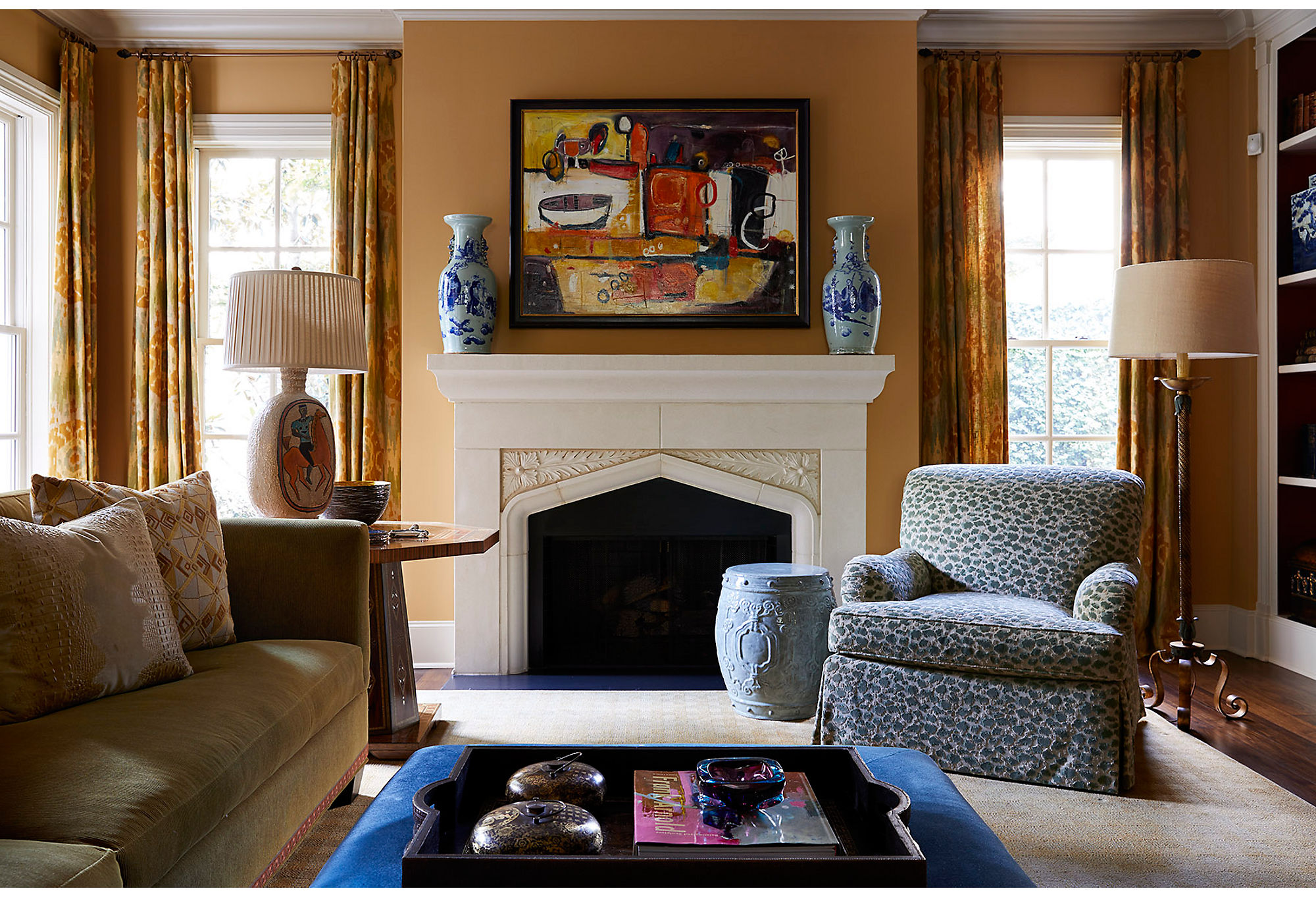 "The den is more subdued than the rest of the house but still filled with color. ""I wanted to make sure that it was welcoming and livable for long periods of time,"" says Dennis. He masters the mix by pairing chinoiseries vases with a modern painting and a Southwest-inspired lamp."
