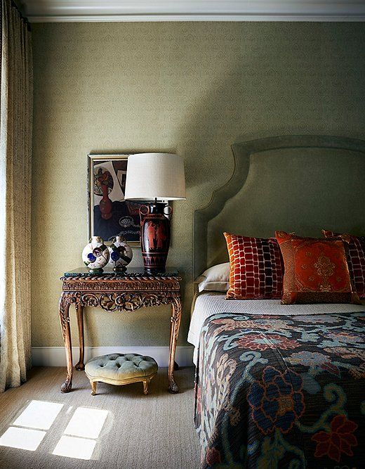 Dennis plays with scale in the master bedroom. An oversize headboard pairs with a tall bedside table and an even taller table lamp.