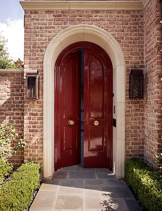 The arched front door, painted a not-so-subtle glossy wine red, gives just a hint at the maximalist interiors that lie beyond.