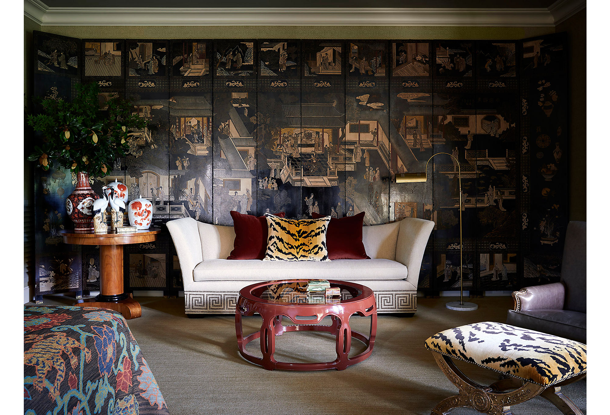No master suite is complete without a sitting area. Here, Dennis covered the entire wall with a 12-panel chinoiserie screen. He pulls in more traditional elements with Greek key detailing on the sofa.