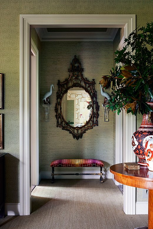 """Every space in the house offers a chance to layer. The entrance of the master bedroom features an ornate mirror paired with a set of decorativecrane sculptures. """"Things should look collected but never unnecessary,"""" Dennis says."""