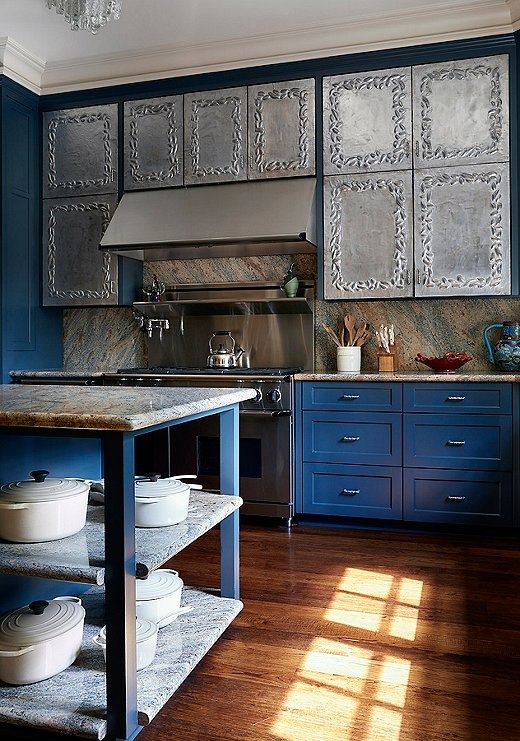 "The kitchen is a maximalist's dream. The silver repoussé cabinetry features a unique floral design. ""Although I would love to take credit, these were actually left in the house by the previous homeowner,"" says Dennis. ""I can take credit, however, for insisting that they remain."""
