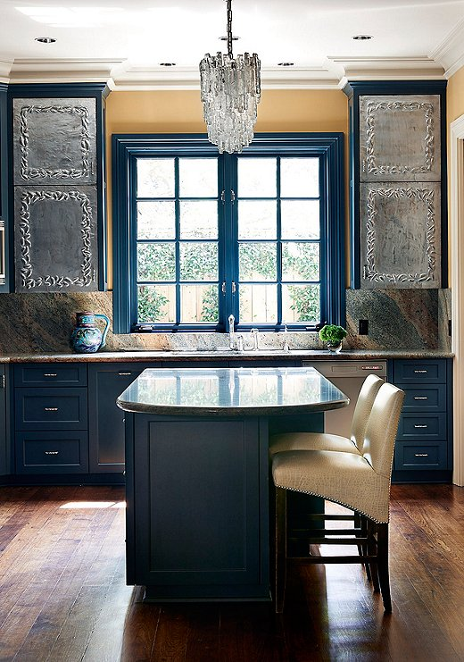 """""""We painted over all the stained cabinetry to give it a fresh look,"""" Dennis says. The multihue marble backsplash purposefully plays off the blue cabinetry."""