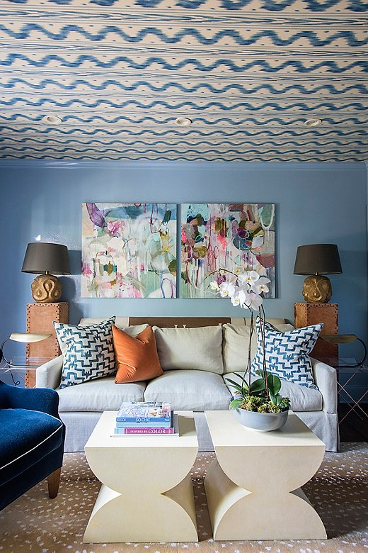 Courtland grew up with a Stark Fauna rug and knew it had to go somewhere in her house; she added it to the pattern-filled den. Orange and blue pillows pull the space together with a conscious play on color.