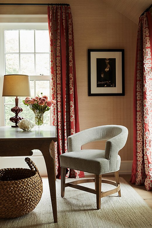 The red curtains in the office add jolt of color toan otherwise subdued palette.