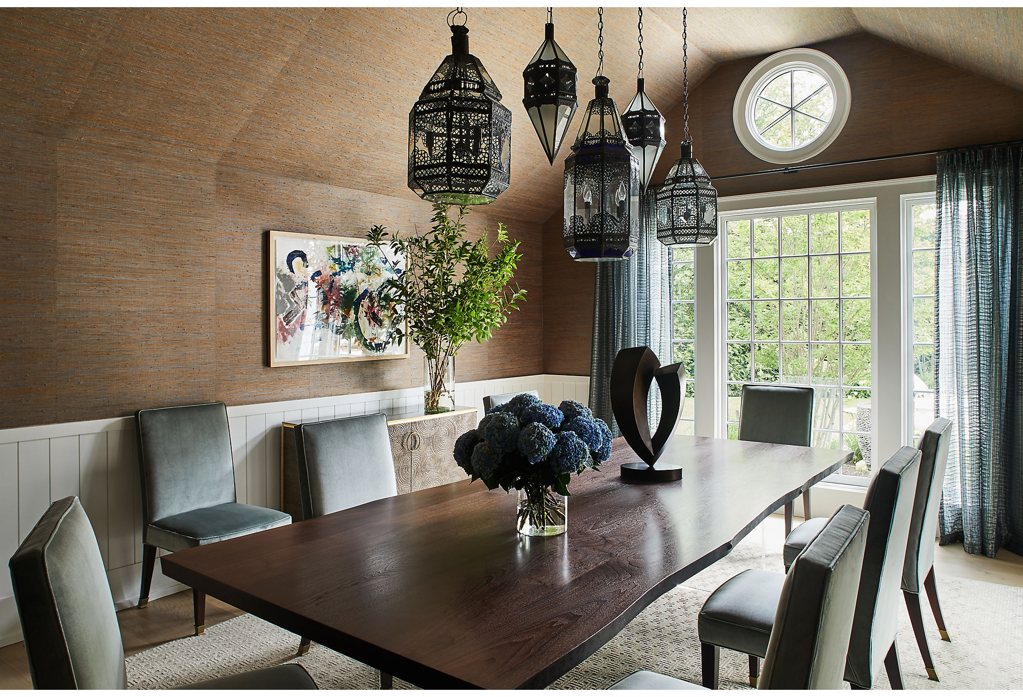 Mara and Jesse kept the owners' antique lights but gutted everything else in the dining room. The color palette feels classic with moody browns and soft blue accents, but the furniture leans more modern.