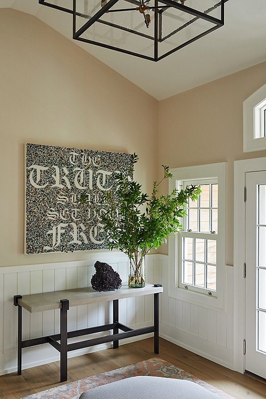 """The owners broughtthe artworkhanging over the console table inthe entrywaywith them. The text reads: """"The Truth ShallSet You Free."""""""
